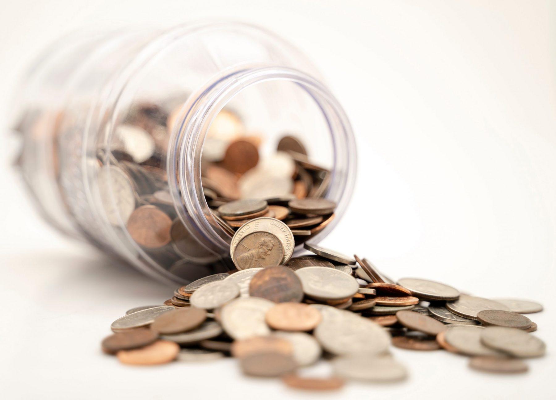 Przewrócony słoik z rozsypanymi monetami