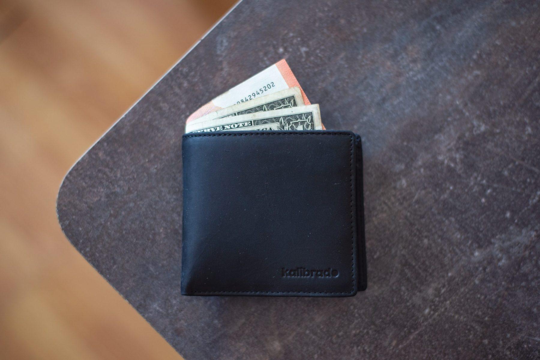 Portfel z banknotami na stole.