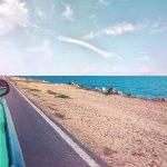 Widok na brzeg morza z jadącego samochodu