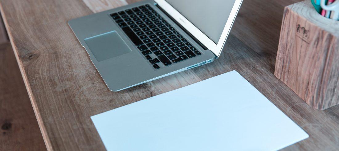 Otworzony laptop, kartka papieru, długopis